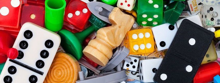 black and white dominoes, chess knights, Ludo piece, dies, and other items used in playing board games