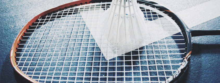 badminton racket and shuttlecock lying on the floor, one of the things you'll need for cheap outdoor games