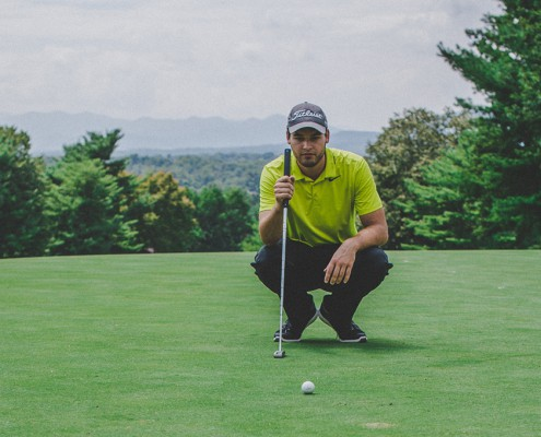 a golfer squat sitting on the lawn and with the golf ball in front of him