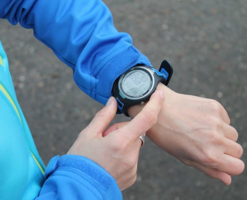 a close-up photo of a person checking the sports watch he is wearing