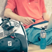 a tennis player with his laptop, energy drink, tennis racket and tennis bag