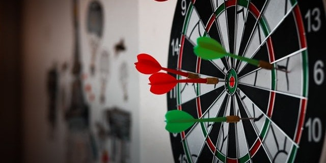 a dart board with lights focused on its dart arrow hitting the bull's eye