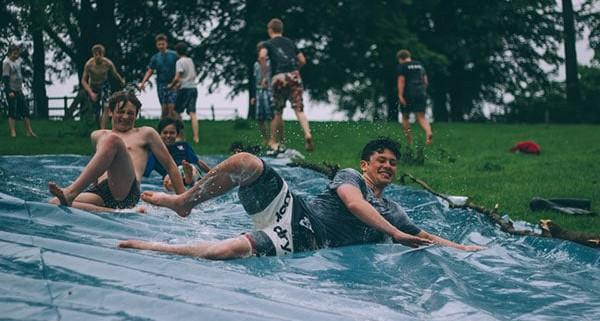 Group of men is enjoying the slip and slide kickball