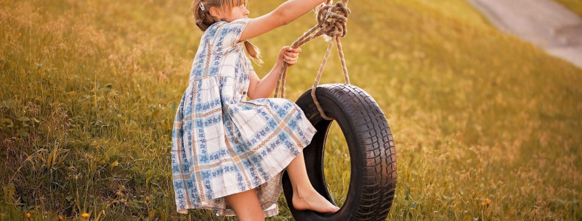 Girl pulling the rope of the tire swing