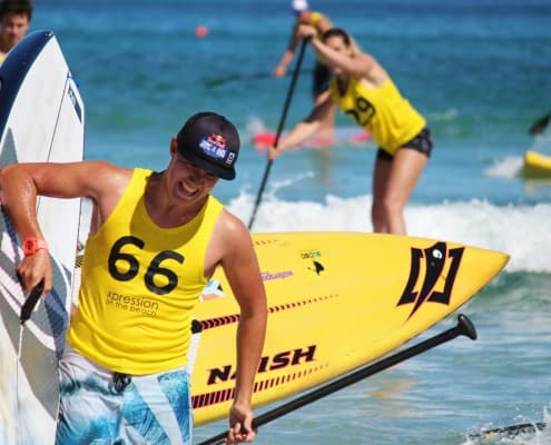 Man holding the best inflatable paddling board while his teammates are paddling it on the ocean