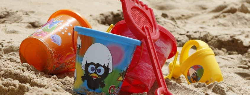 bucket and other toys lying on sand