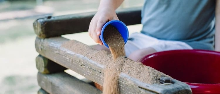 kid pouring sand from a plastic cup